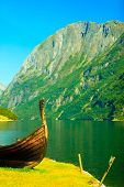 stock photo of viking ship  - Tourism and travel. Mountains and fjord Sognefjord in Norway Scandinavia. Old viking boat ship on seashore.
