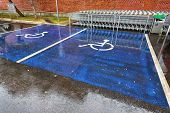 image of handicap  - handicapped parking sign on the road wet - JPG