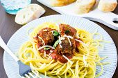 picture of cilantro  - Homemade Italian meatballs garnished with cilantro and parmesan cheese over spaghetti for dinner - JPG