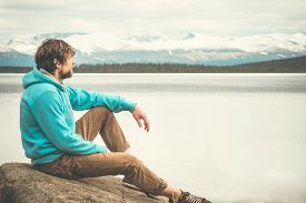 stock photo of boy scout  - Young Man relaxing alone outdoor Lifestyle Travel concept scandinavian mountains and lake on background - JPG