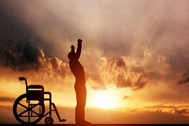 foto of handicapped  - A disabled man standing up from wheelchair at sunset - JPG