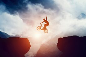 pic of risk  - Man jumping on bmx bike over precipice in mountains at sunset - JPG