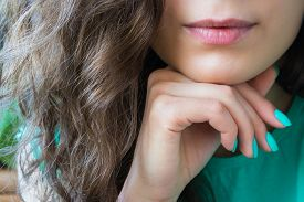 picture of domination  - young beautiful girl with brown shiny hair holds a hand with a turquoise nail polish near the chin lips dyed red lipstick - JPG