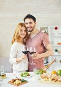 image of amor  - Amorous man and woman toasting with red wine in the kitchen - JPG