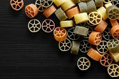 stock photo of wagon wheel  - Dry coloured wagon wheel pasta on black textured wood from above - JPG