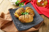 pic of basil leaves  - Baked potatoes with basil leaves on wooden table - JPG