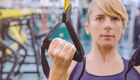 image of suspension  - Closeup of fitness strap in the hand of woman doing hard suspension training in a fitness center - JPG