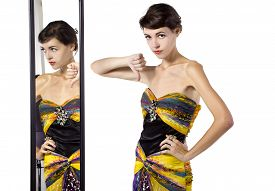 stock photo of snob  - woman wearing a dress with her thumbs down while looking at a mirror - JPG