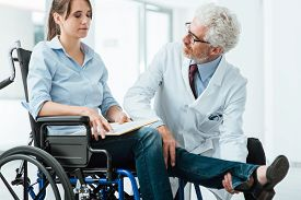 foto of wheelchair  - Doctor visiting an invalid woman in wheelchair he is examining her leg rehabilitation and physioteraphy concept - JPG