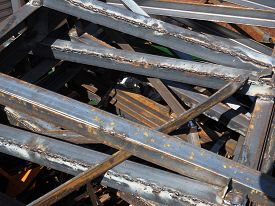 stock photo of scrap-iron  - Pile of various sized scrap iron profiles in a scrap metal pile used for industrial transport packaging with slight rust - JPG