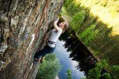 Постер, плакат: Женской альпиниста на крутой скале ищет следующий hold Малая глубина резкости используется для