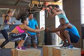 Instructor giving encouragement while fit strong healthy people do box jumps in crossfit gym poster