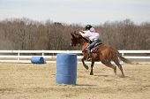stock photo of barrel racing  - A young woman races to the finish after rounding a barrel  - JPG