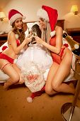 foto of promiscuous  - Two sexy girl to have taken Santa Claus like prisoner and   clinking glasses of champagne - JPG