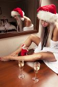 image of promiscuous  - Portrait of two sexy girls in Santa hats with the glasses of champagne waiting for New Year - JPG