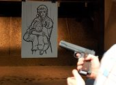 image of shooting-range  - Male shooter and target - gun in hand.