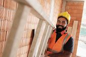 Portrait Of Happy Hispanic Worker Smiling In Construction Site poster