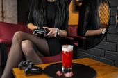 Young Woman In A Black Dress Sits In A Bar With Cocktail Holding A Black Joystick In Her Hands And P poster