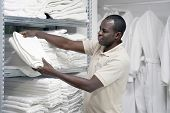 Hotel Worker African Man Lays A Clean White Towel On The Shelves. Hotel Staff Workers. Hotel Linen C poster