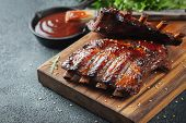 Closeup Of Pork Ribs Grilled With Bbq Sauce And Caramelized In Honey. Tasty Snack To Beer On A Woode poster