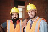 Happy Construction Workers Smiling At Camera In New Building poster