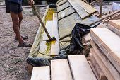 Worker At A Construction Site At Home Covers Antiseptic Boards. Impregnation Of Boards. poster
