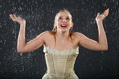 stock photo of jupe  - happy beautiful girl wearing in dress smiles in rain and catches drops by hands - JPG