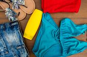 Set Of Beachwear On Wooden Background. Sunscreen, Towel, Blue Bikini, Sandals And Jeans Shorts. Summ poster