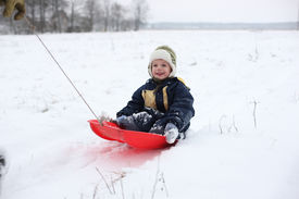 picture of winter sport  - Winter joy - small kid in red sledge during snow