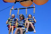 stock photo of parasailing  - Father and Twin Daughters Parasailing Against a Blue Summer Sky - JPG