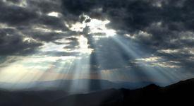 stock photo of sun rays  - Bright sun rays struggling through dark storm clouds - JPG