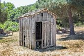 stock photo of outhouse  - Dilapidated and Abandoned Outhouse in the American West.