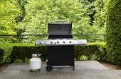 picture of house woods  - Horizontal photo of large barbeque cooker with lid up on concrete outdoor patio with woods background - JPG