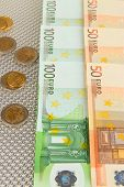 Euro banknotes and euro cents on grey background
