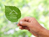foto of reprocess  - Eco house concept hand holding eco house icon in nature - JPG