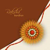 stock photo of rakhi  - Beautiful rakhi design on brown and beige background on the occasion of Happy Raksha Bandhan - JPG