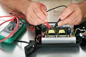 pic of circuits  - a person uses a voltage meter to check for dead circuits - JPG