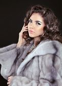 foto of mink  - Beautiful brunette woman in mink fur coat isolated on black background - JPG