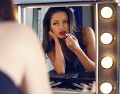 image of mirror  - fashion interior photo of beautiful sensual woman with dark hair doing makeup in makeup roomlooking at the mirror