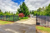 pic of driveway  - House exterior with open iron gate driveway and garage - JPG