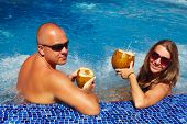 foto of hot-tub  - Couple with coconut drink relaxing in hot tub - JPG