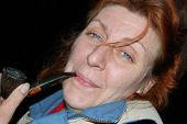image of peace-pipe  - Face of mature lady resting outdoor at late evening with old pipe - JPG