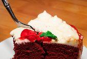 pic of red velvet cake  - Fork diving into a red velvet cake on a white plate - JPG