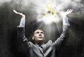 pic of exaltation  - Businessman praying at dollar sign above - JPG