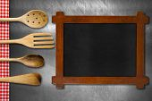 foto of ladle  - Rustic and empty blackboard four wooden kitchen utensils fork spoons and ladles on brushed metallic background with red and white checkered tablecloth - JPG