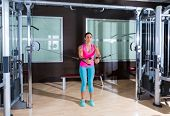 foto of pulley  - Standing cable crossover fly pulley flies woman workout at gym - JPG
