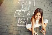 stock photo of hopscotch  - beautiful cheerful little girl playing hopscotch on playground outside - JPG