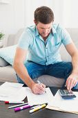 stock photo of concentration  - Concentrate man at home counting his bills in a sofa - JPG