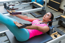 picture of pilates  - Pilates reformer workout exercises woman brunette at gym indoor - JPG