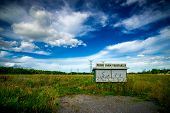 pic of shacks  - A small abandoned produce vendor shack with a sign reading Fresh Farm Vegetable stands amidst the wild overgrowth in a green meadow - JPG